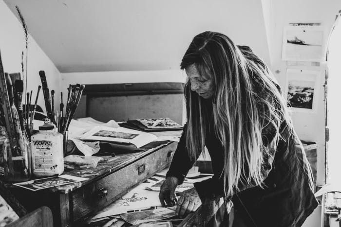 black and white image of woman in art studio with assorted paint brushes and reference images strewn about and tacked to wall