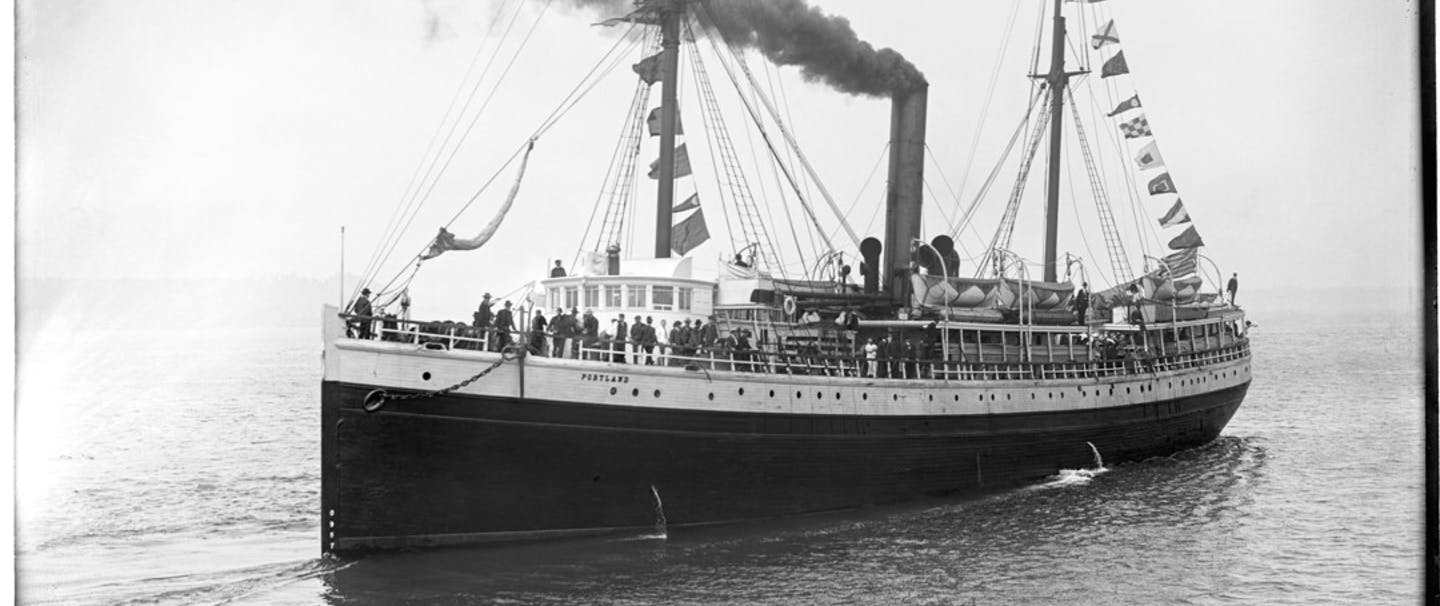 Large Steamship at sea with smoke billowing from a central smoke stack