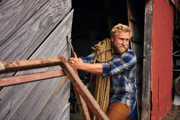 blonde man closing a large wooden barn door with a large coil of rope over his shoulder