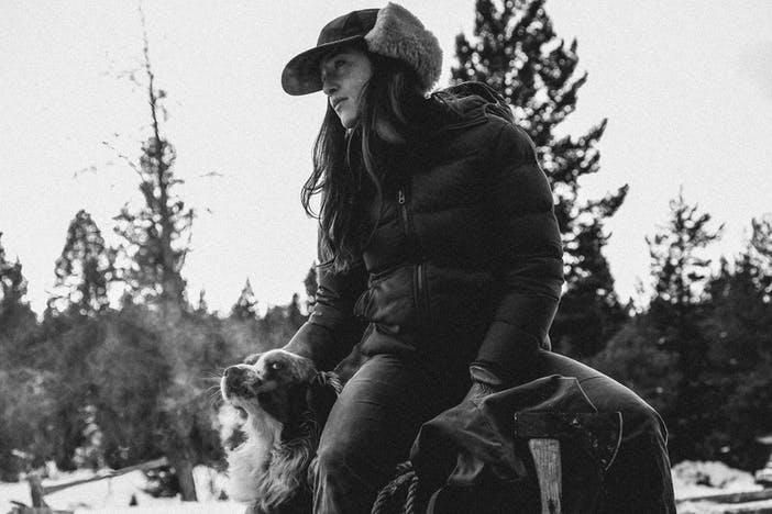 black and white portrait of woman in filson mackinaw double ear flap hat sitting next to dog in woodland area