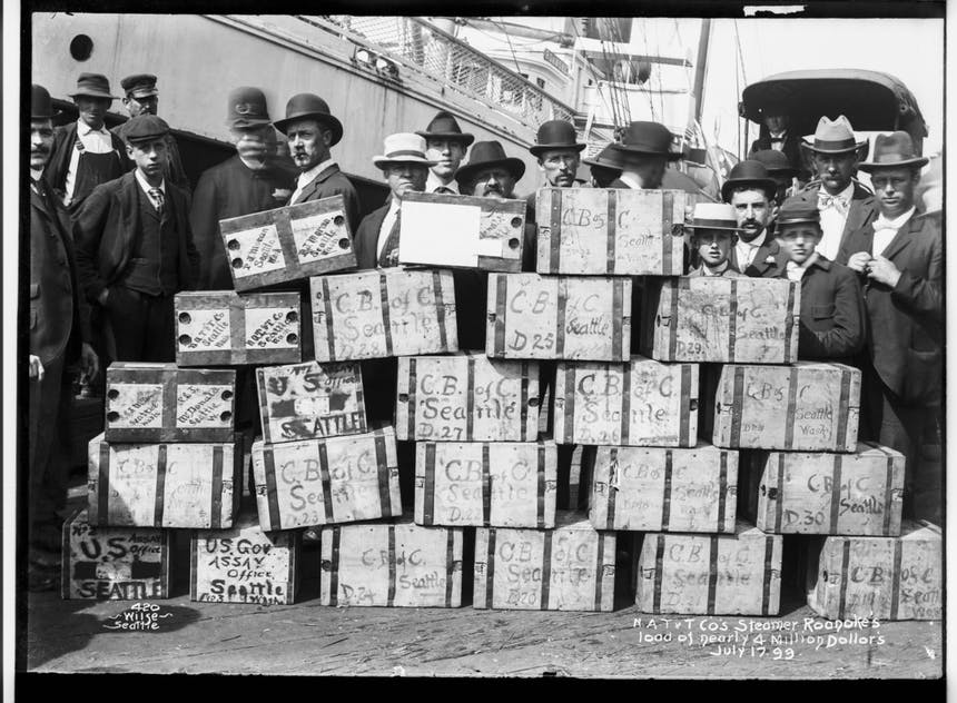Men in suits and some police officers standing behind a stack of boxes reading CB of C Seattle