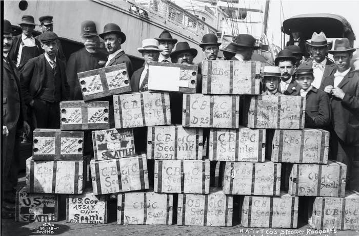 black and white image of people in antiquated clothes and hats standing behind a large stack of bound wooden boxes reading