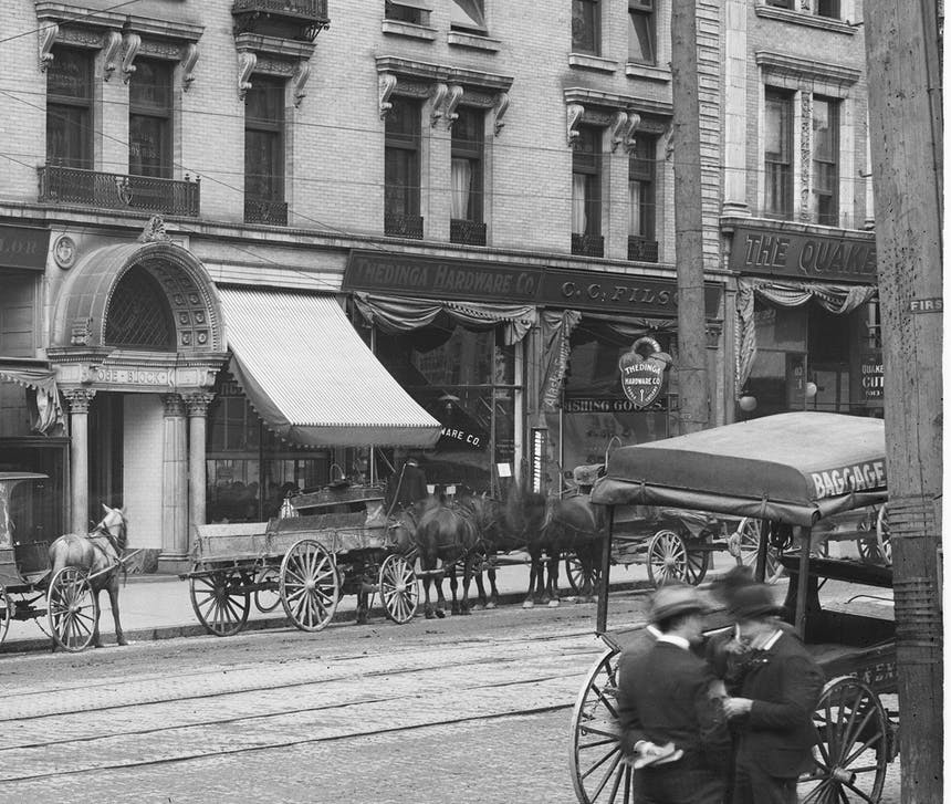 vintage image of CC Filson Storefront with horse drawn carriages on cobbled street