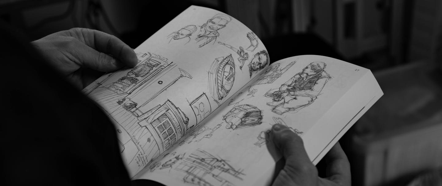 black and white image of hands holding a sketchbook with sketches of people, boats, and camping equipment