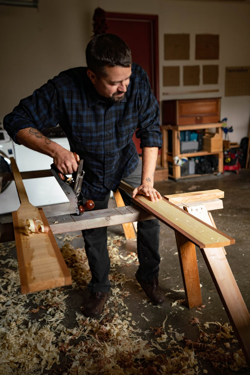 man working on wooden paddles balanced on two sawhorses shaving them down leaving wood shavings on floor