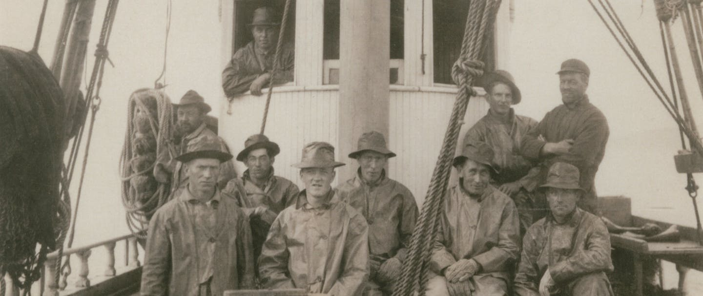 vintage black and white image of 8 members of the Deep Sea Fishermens union on their boat in uniforms