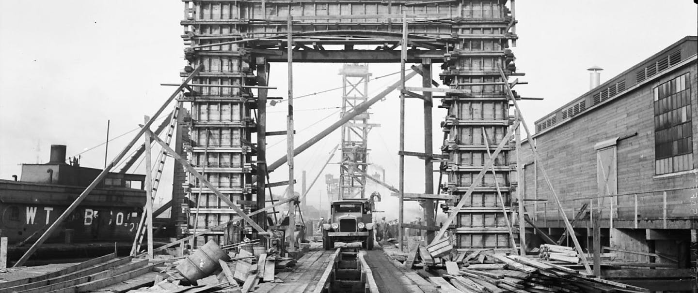 black and white image of an old car driving across the wooden structure underneath a scaffolded square arch