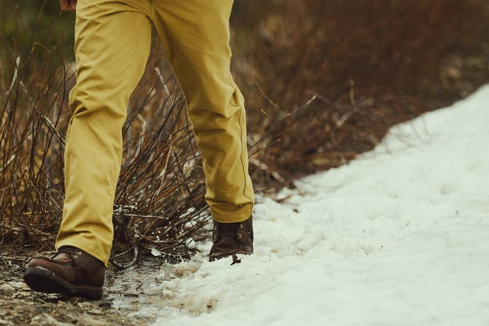 closeup of person walking through snow with dog in foreground wearing dry tin dark tan pants