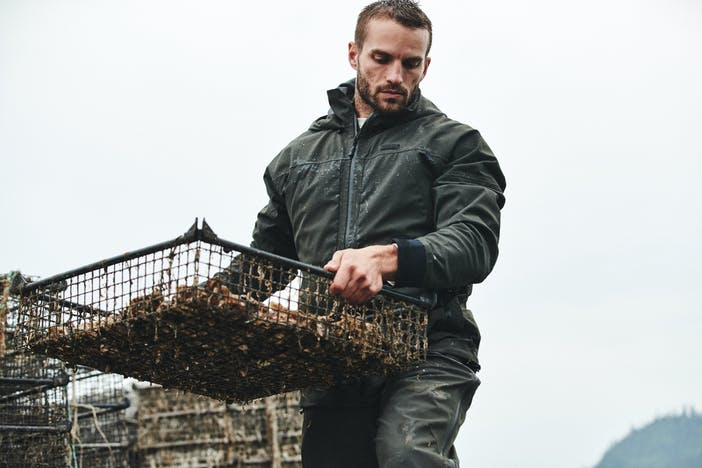 man in green filson jacket holding a square crab trap box
