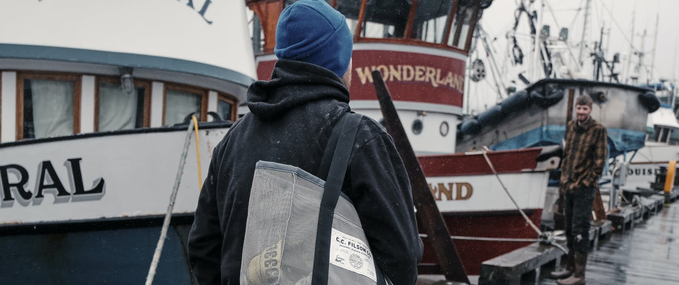 person tan pands and brown boots with canvas bag walking along a wooden dock next to small fishing vessels