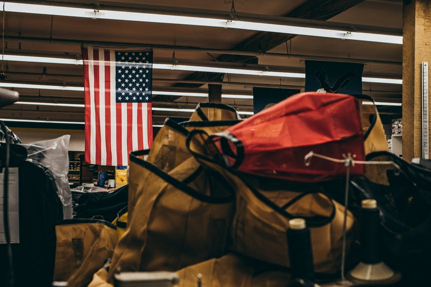 bags stacked in a warehouse with an american flag hanging from the rafters