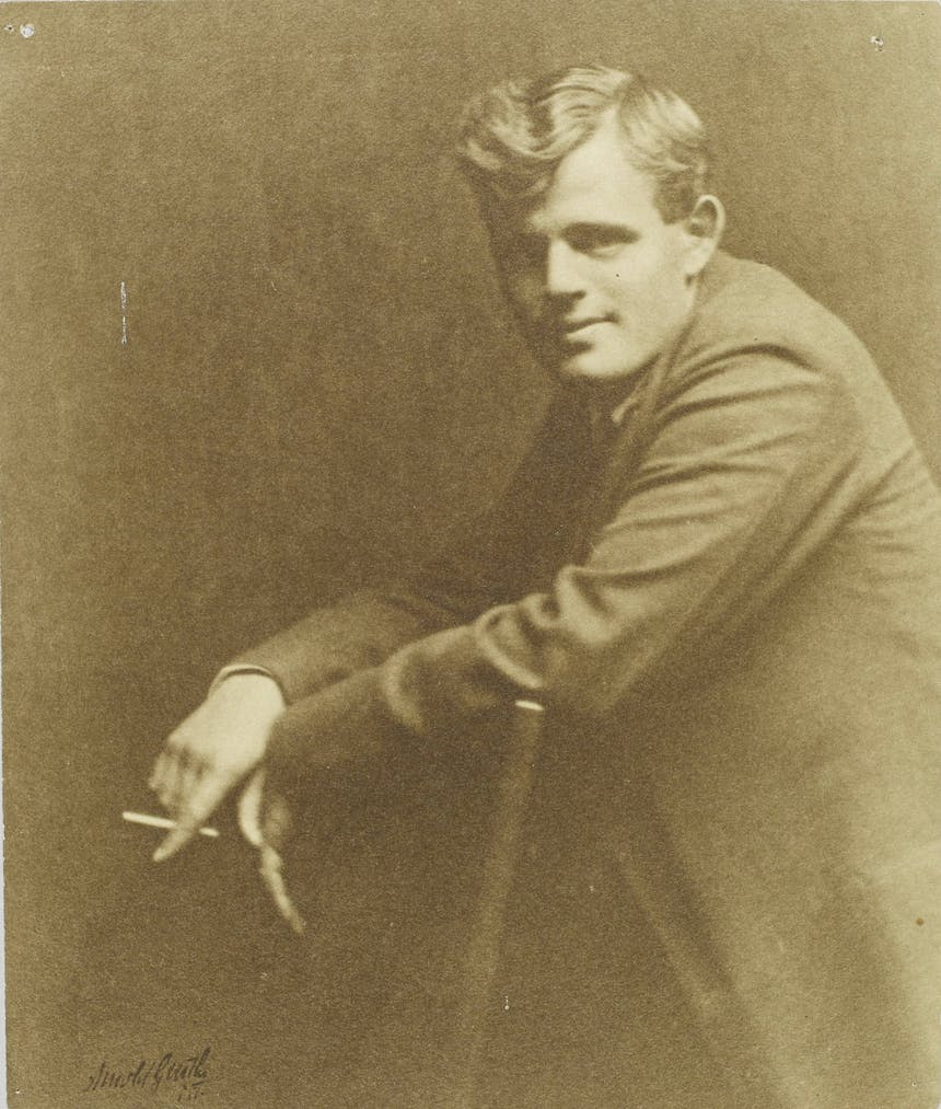 Portrait of Jack London from side, he leans over back of chair with cigarette in hand