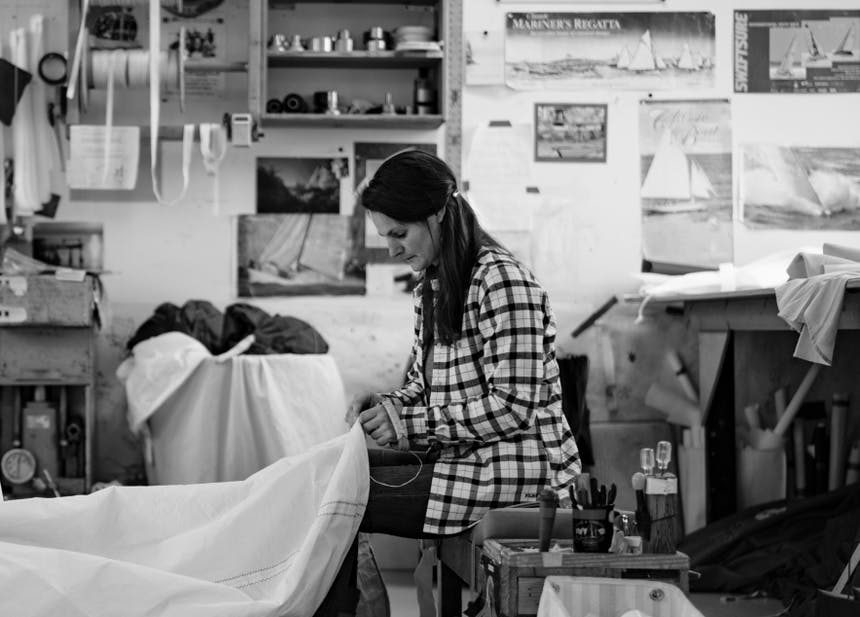 black and white image of woman in plaid shirt repairing a sail with thread and needle in a studio