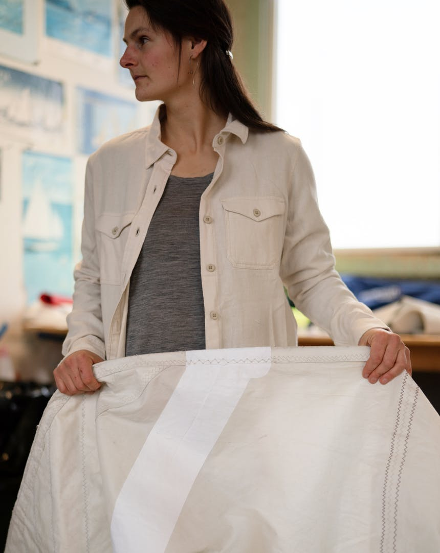 woman in white button up shirt and grey undershirt holding a white canvas sail with repair tape sewed onto a portion