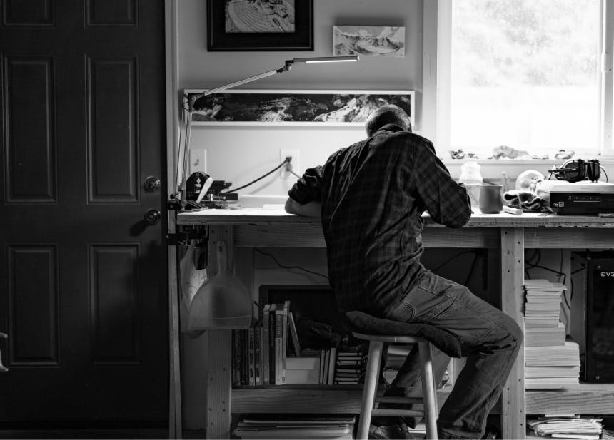 man sitting at a workbench with a light sketching