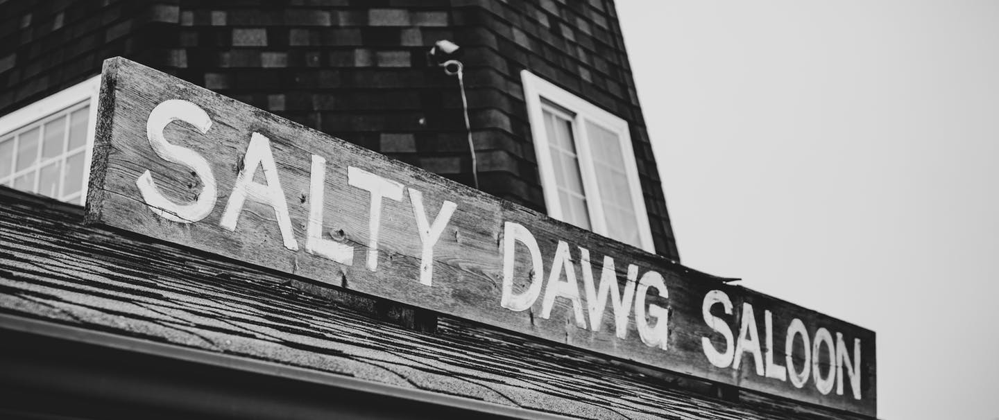 black and white image of white block letters of the Salty Dawg Saloon Sign