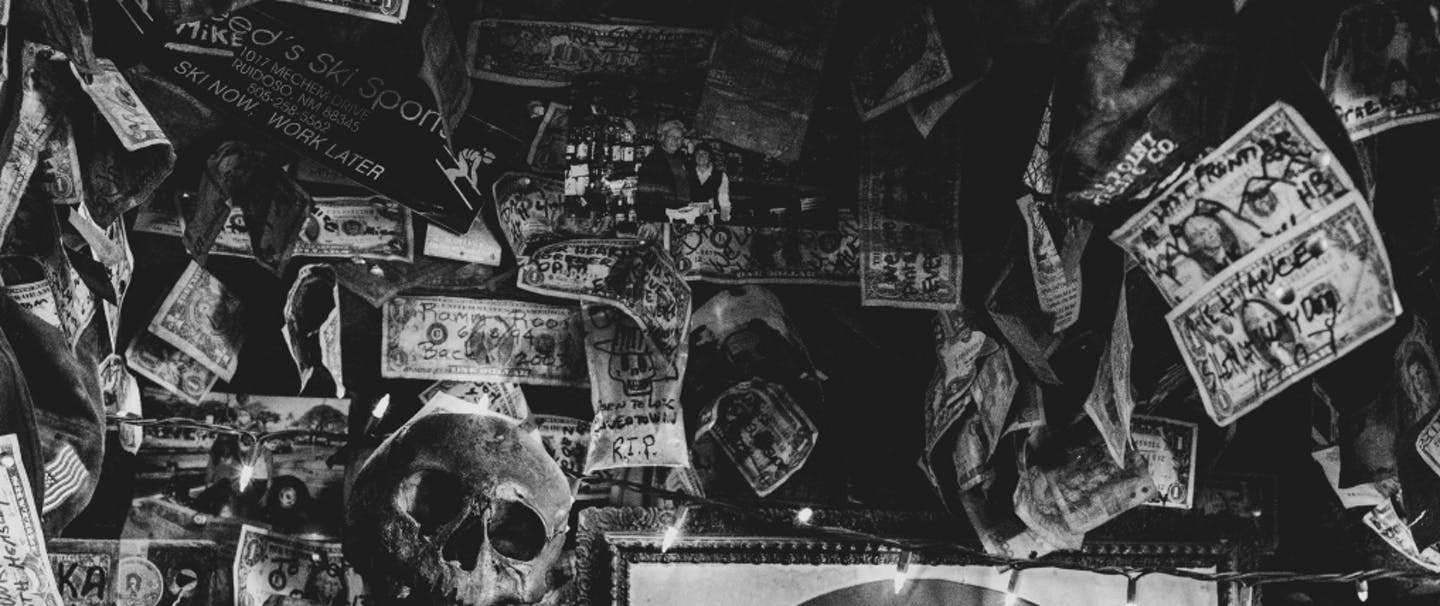 image of eclectic decor of the backbar at the salty dog saloon, human skull, old pinup portraits, and money hung everywhere