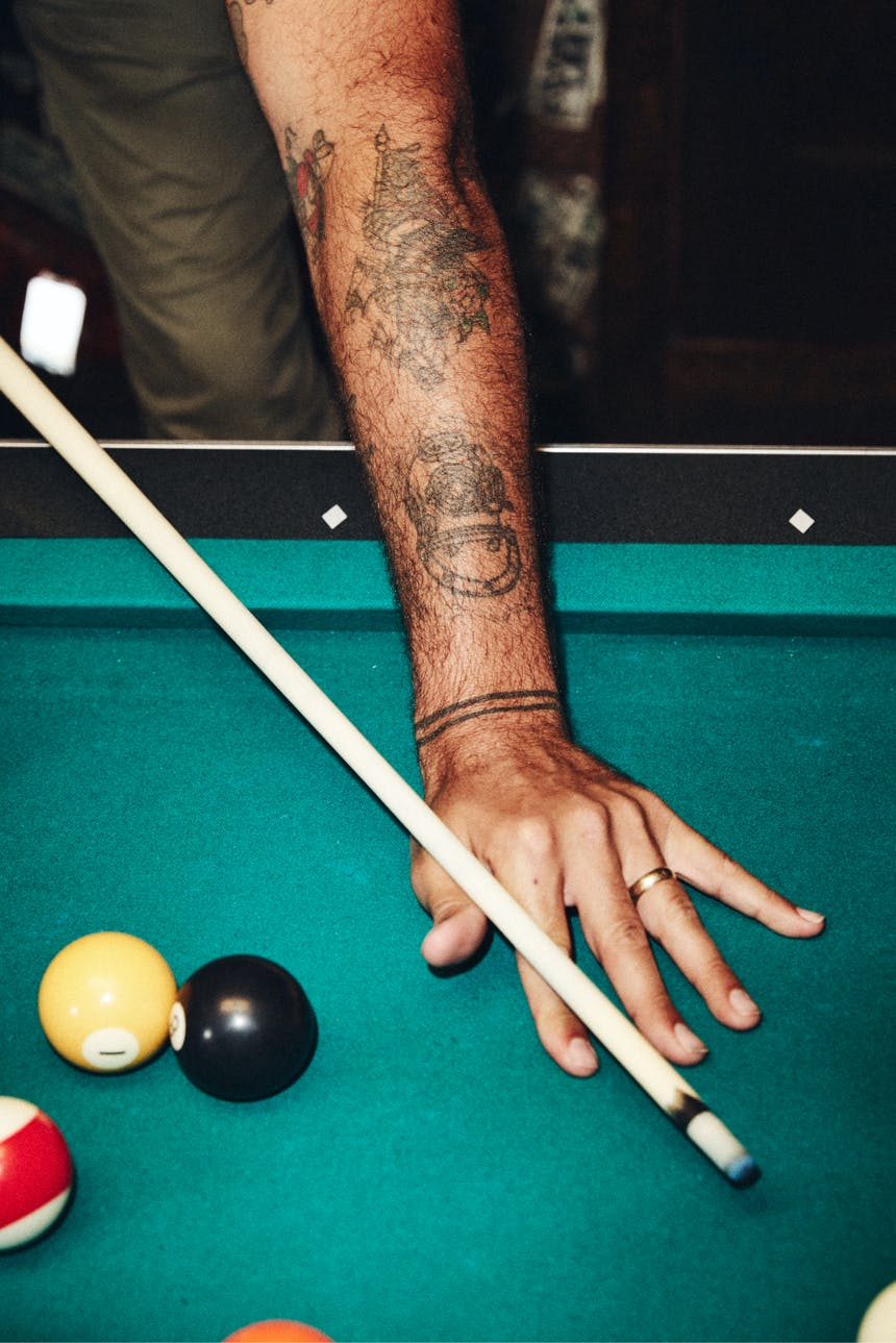 forearm with sailor tattoos preparing a pool shot with cue
