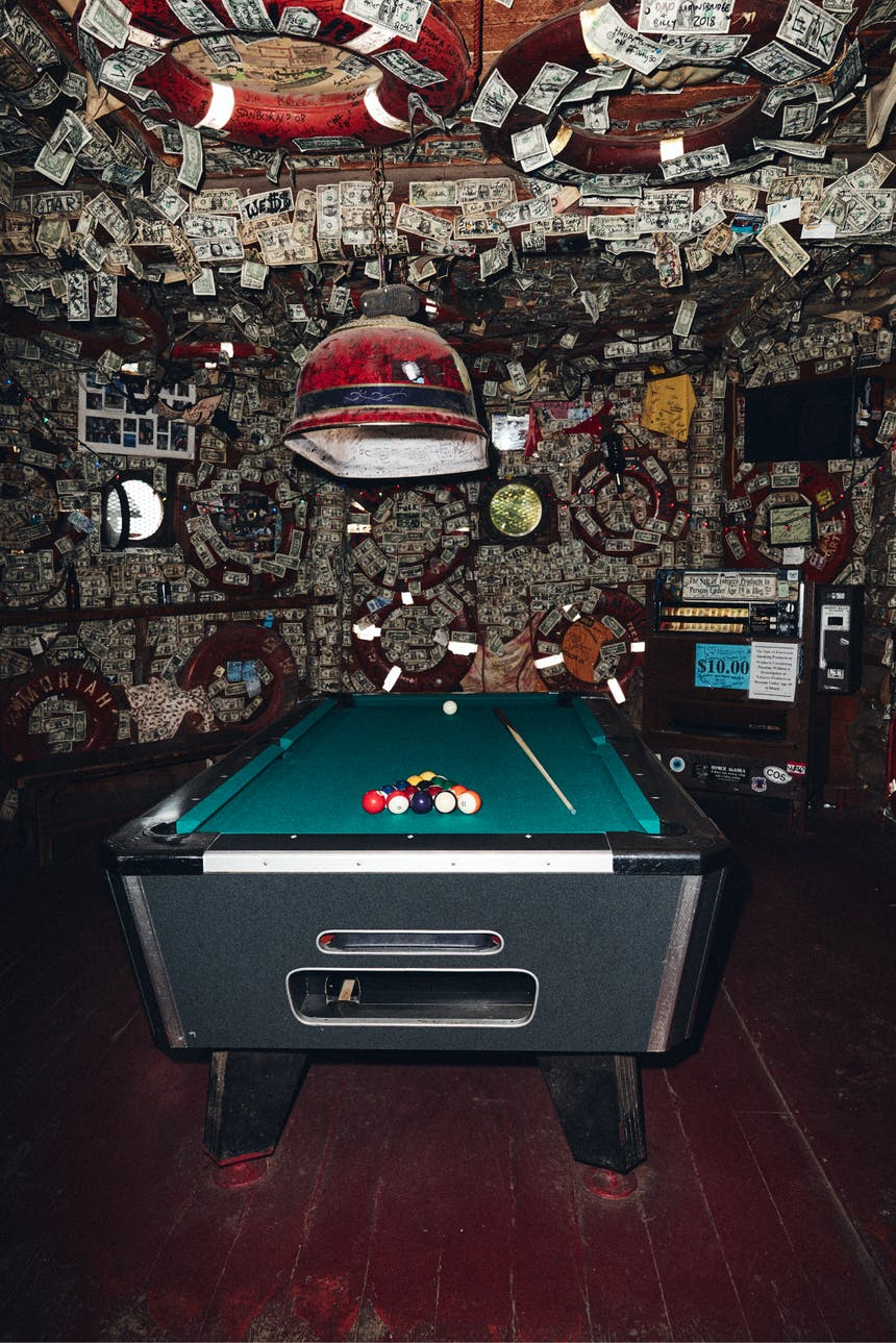 pool table at an eclectic looking dive bar with a wall and ceiling covered in money and port hole windows that have been boarded up in background