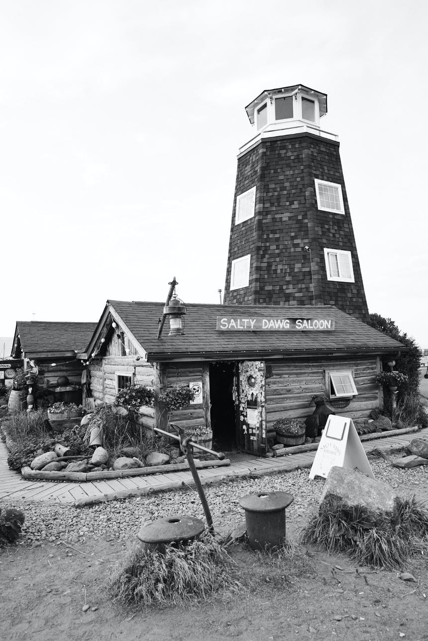 black and white image of salty dawg saloon with lighthouse rising from the back