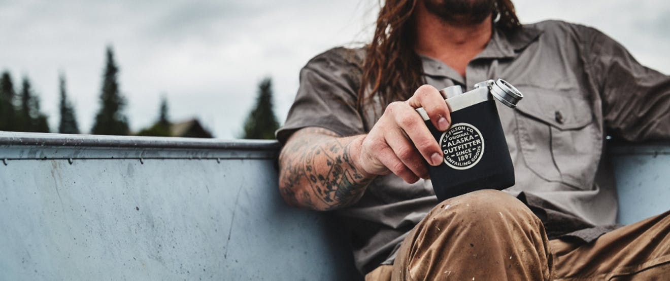 man with tattooed forearm's hand holding a CC Filson Co. Flask while sitting in a boat