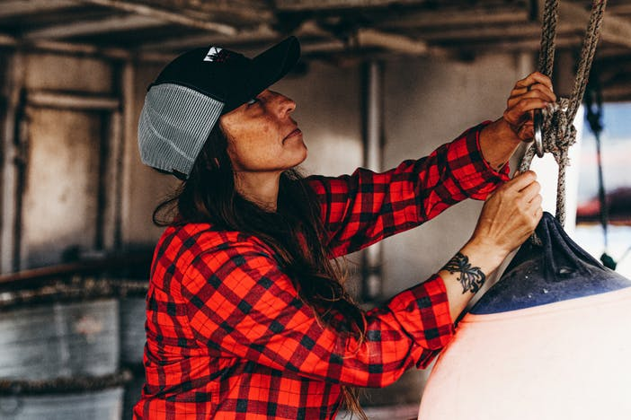 woman in blue filson trucker hat and red flannel shirt tying a floatation device to a suspended hook with cord