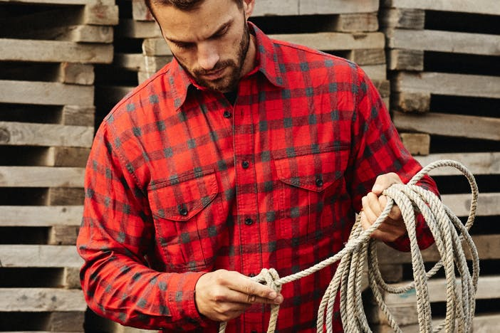 man in red plaid shirt in front of stacked wood holding a coiled rope