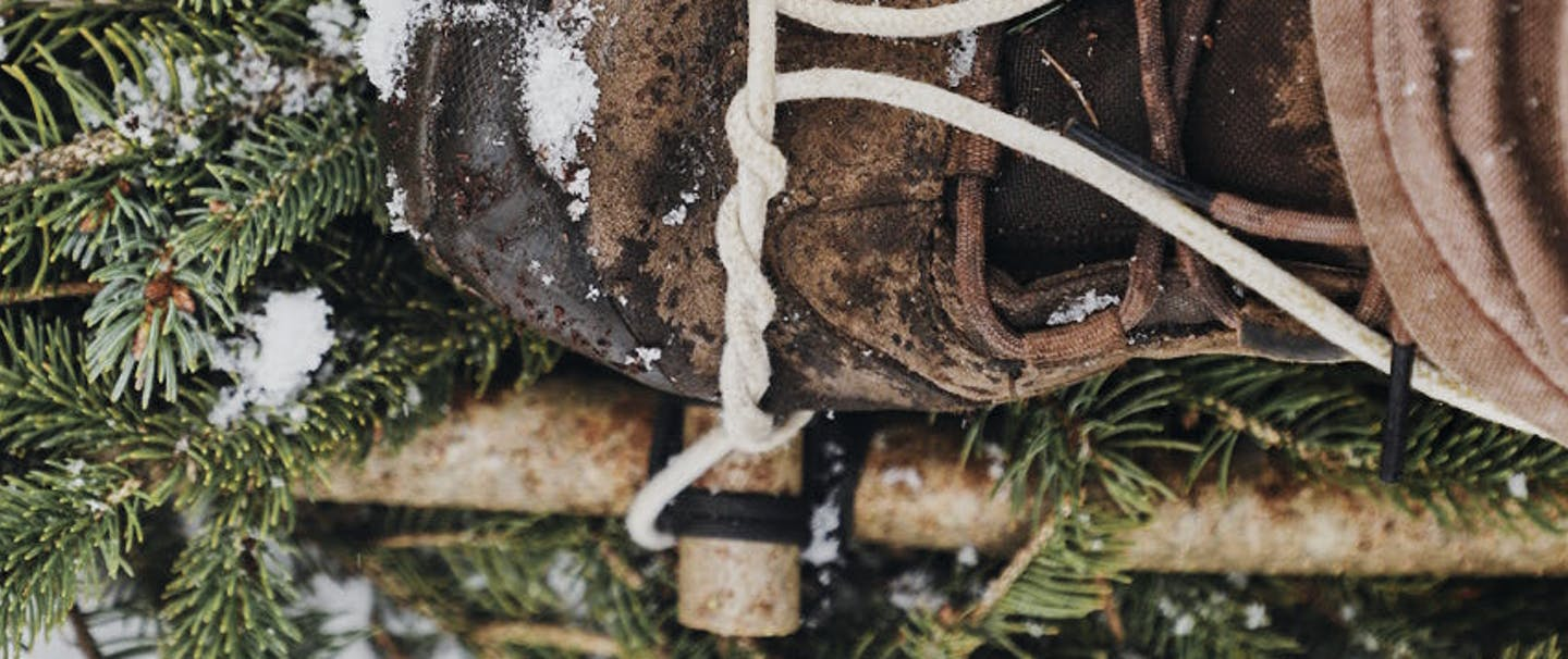 boot in improvised snowshoe made out of lashed pine boughs