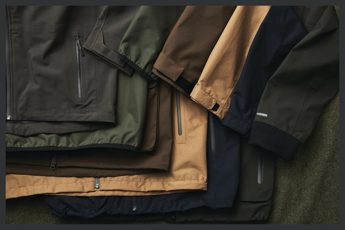 filson rain proof jackets laid out on cloth surface various colorways olive green, tan, navy, brown, etc.
