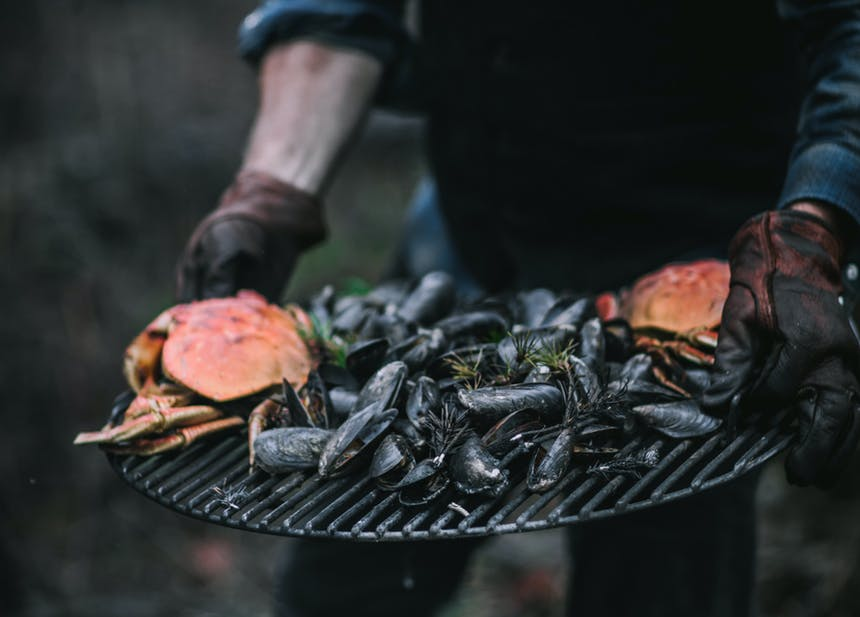 gloved hands holding a round grate with cooked mussels and two crabs on top