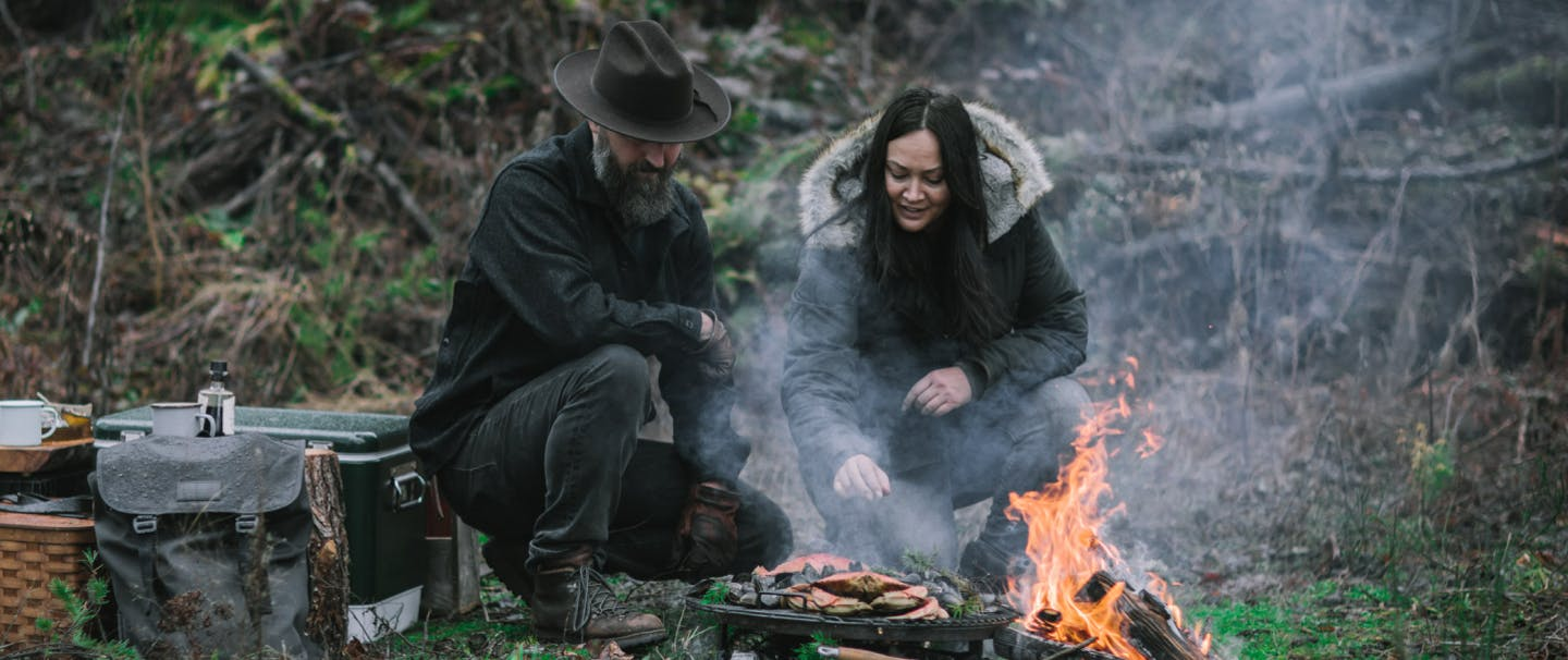 man and woman in woods kneel next to seafood cooking over an open fire next to a cooler and filson bag