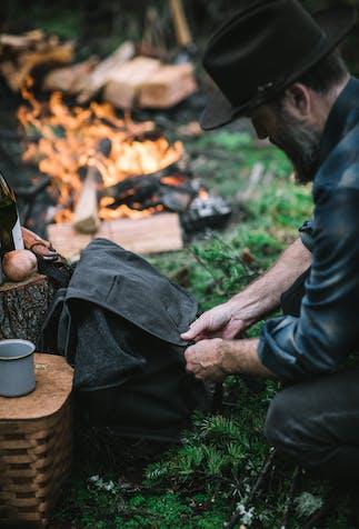 man kneeling in front of an open fire preparing food