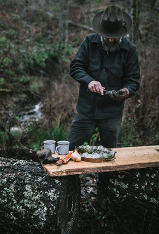 man in brown hat and green jacket shucking oysters in the woods