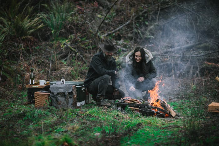 two people in lush mossy forested area tending to food cooking by an open fire