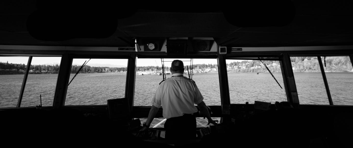 captain of boat standing at the bridge with a map spread out on the central console looking out at a pine ridged beachhead