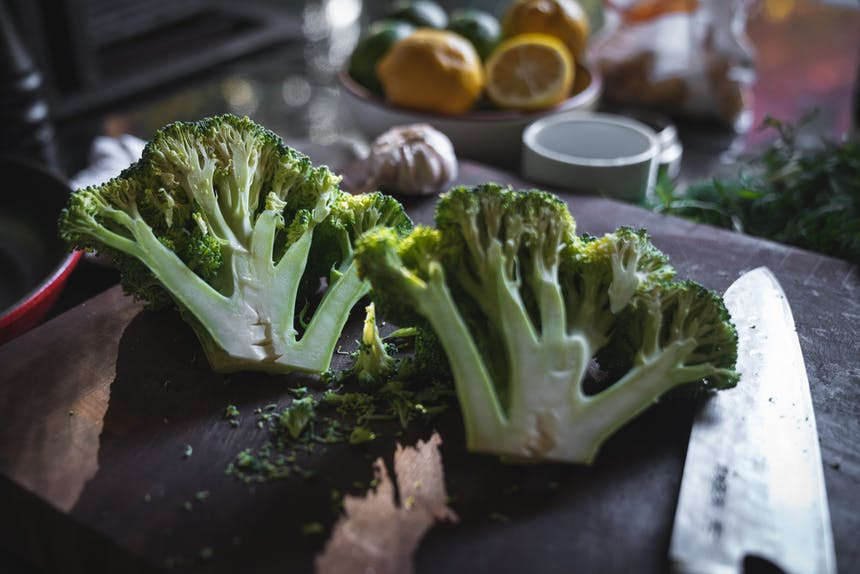 halved head of broccoli on wooden cutting board with bowl of citrus in background