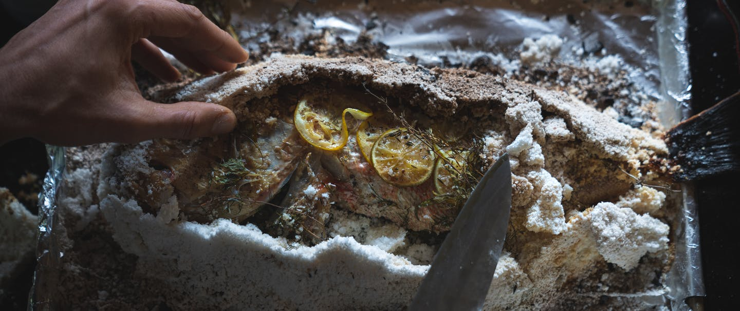 hand removing salt crust from a baked fish with lemon and herbs exposed on top of the fish skin