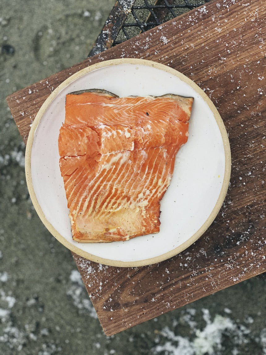 top down view wild salmon filet on a white plate on a wooden cutting board over a sandy beach