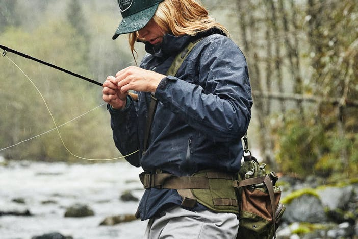fly fisherwoman with blue waterproof jacket and waist/crossbody gear bag on stands in river tying a fly to her line