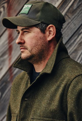 man in filson trucker hat and olive colored coat