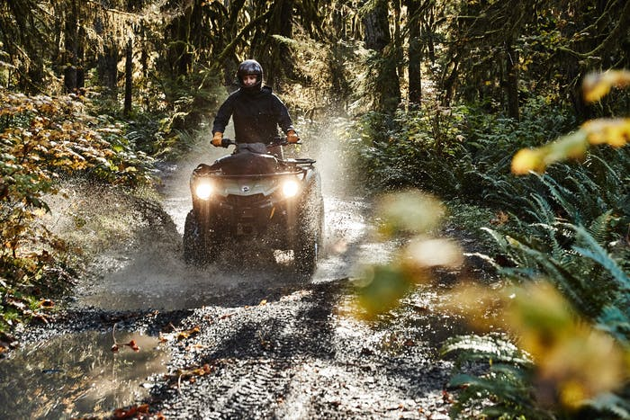 man driving atv splashing through puddle on dirt road in a mossy forest
