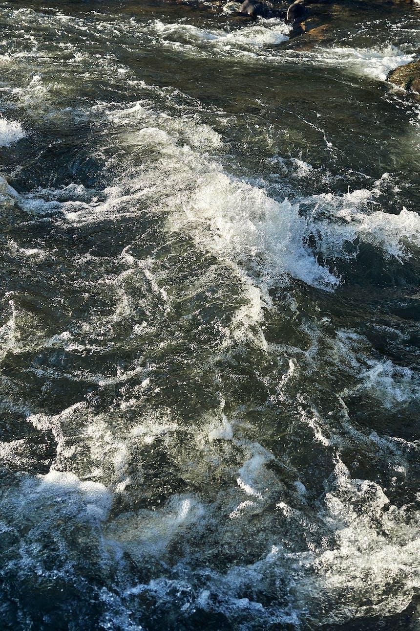 white water rapids in dark river water