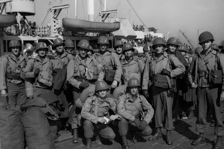 vintage image of a group of soldiers with numbers written in chalk on their helmets standing on the deck of a military ship