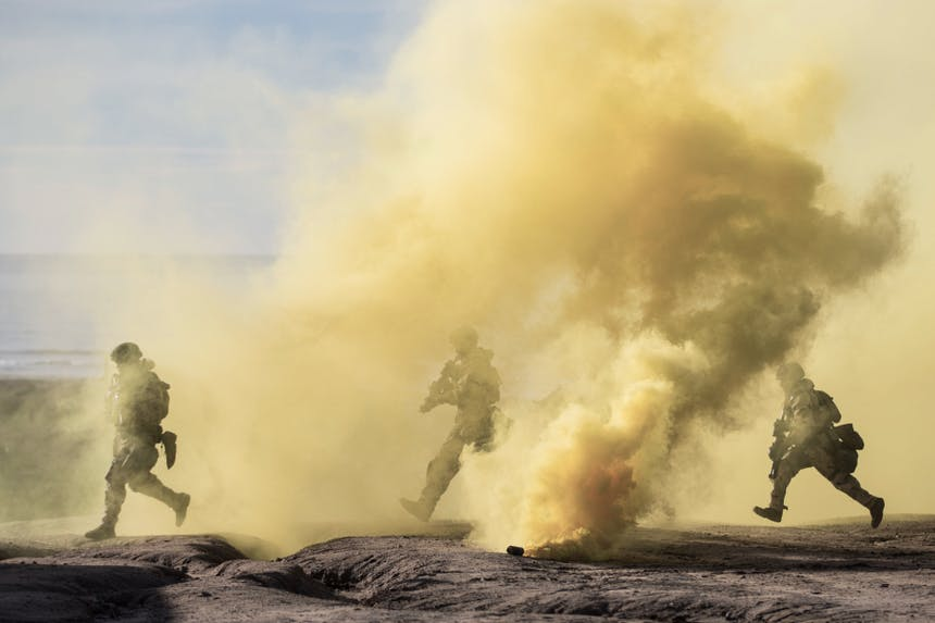 three soldiers in full combat gear running through a barren landscape full of a cloud of smoke emanating from a smoke grenade