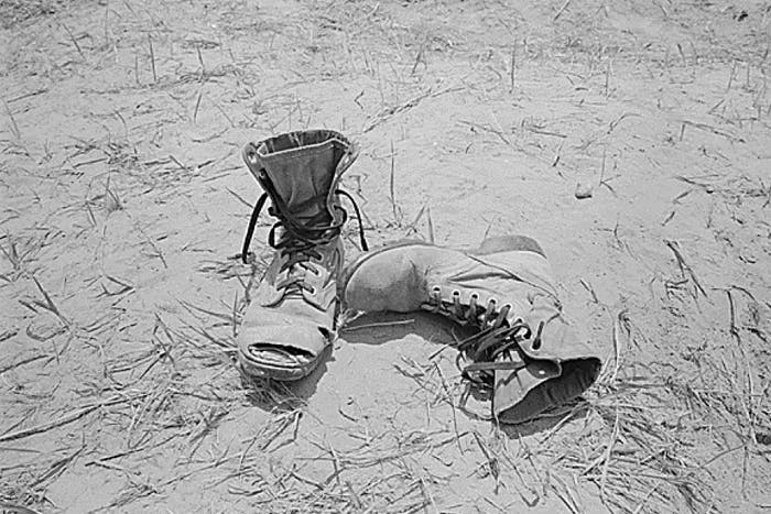 black and white boots on a dusty and grassy ground