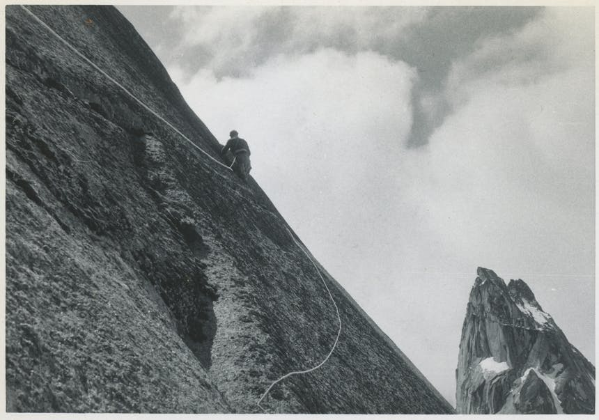 black and white image of an early mountain climber tied to a rope on a sheer granite mountain face