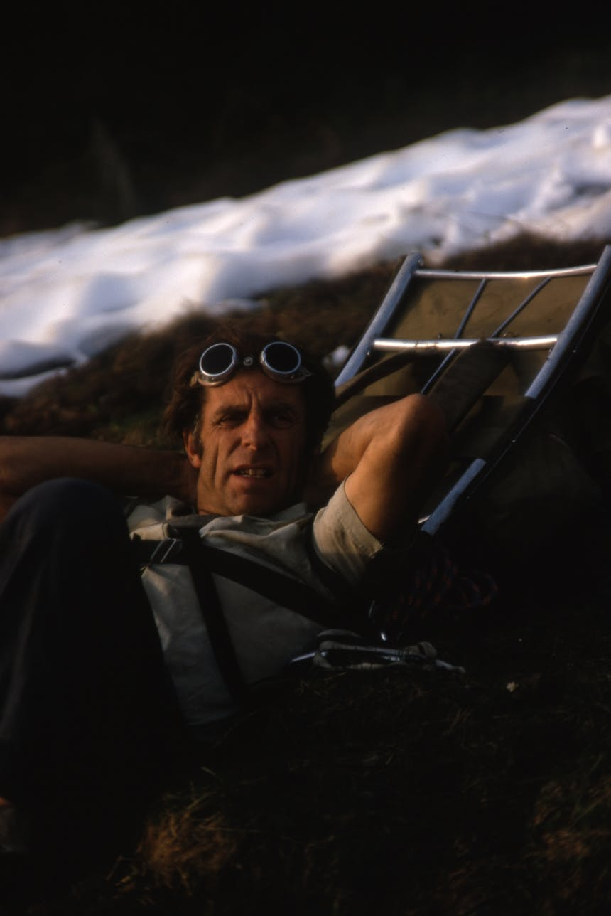 portrait of fred beckey with alpinist glasses on his forehead relaxing using his backpack as a pillow on a snowy mountainside