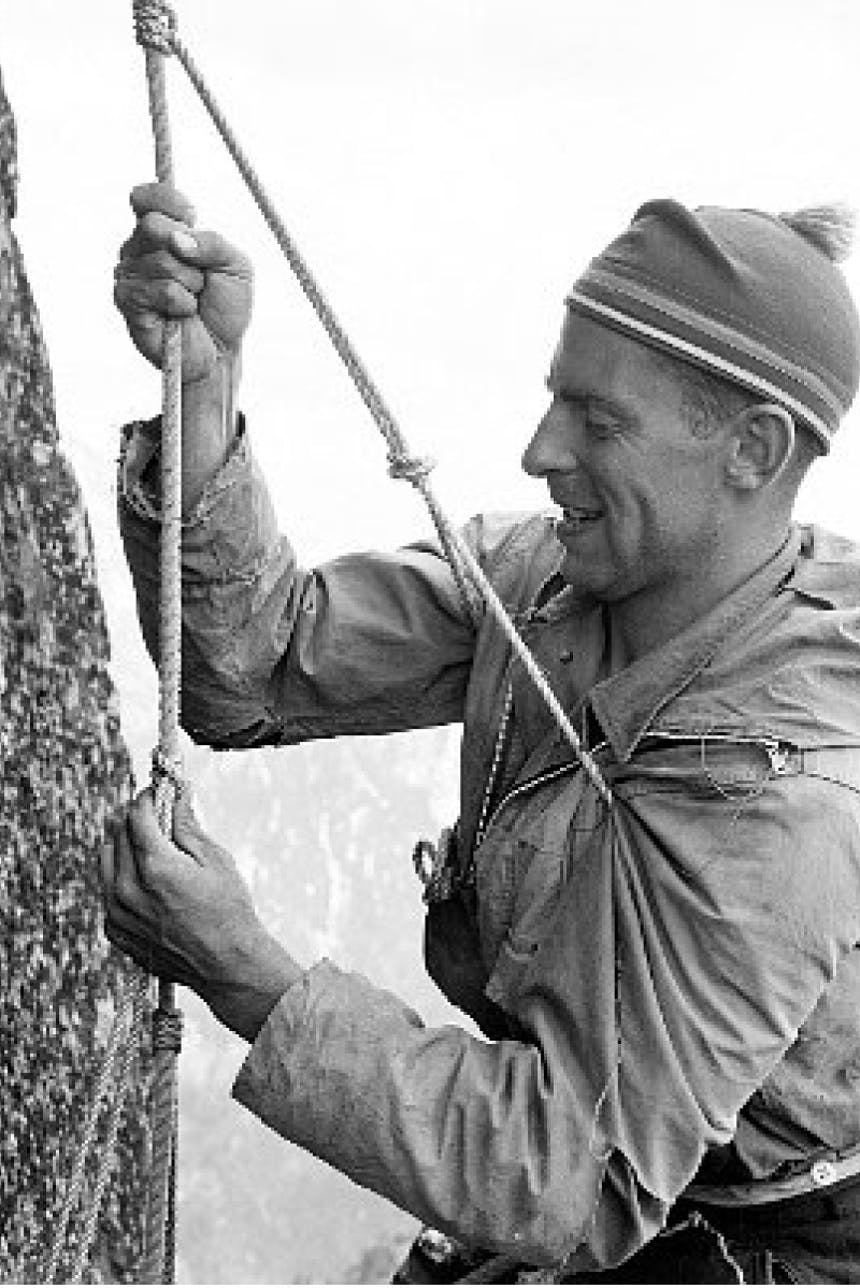person hanging on a rope tied to a granite rock face