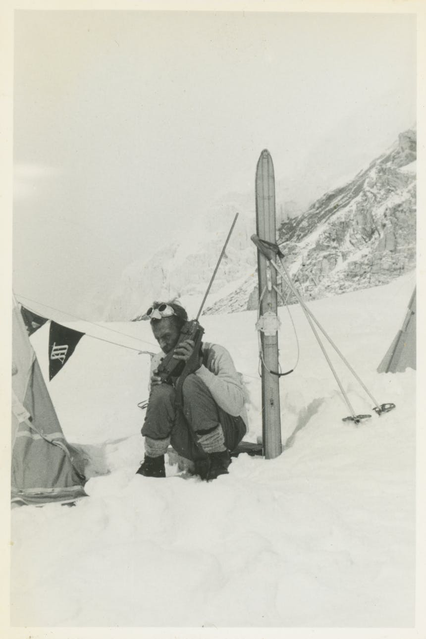 Fred Beckey sitting in a snowy mountainside holding a large wireless phone up to his ear