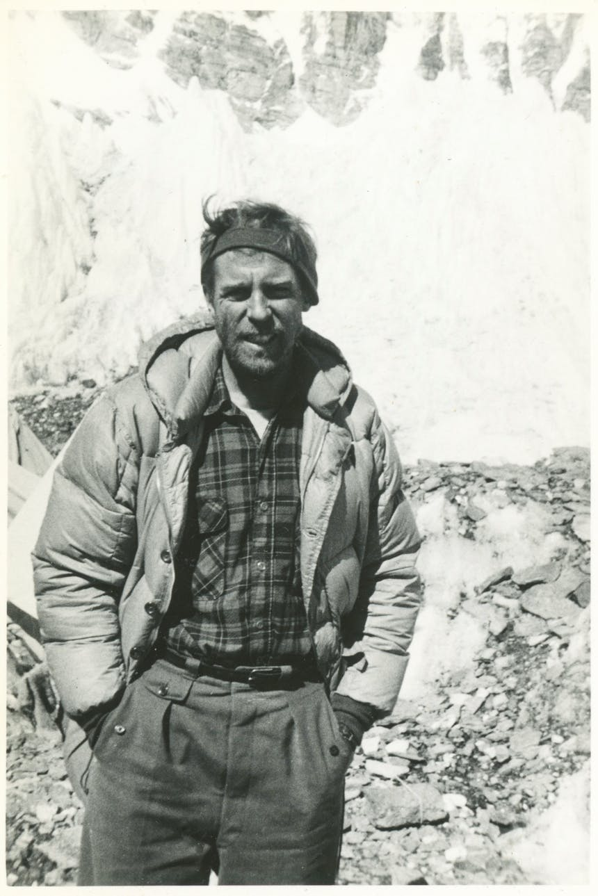 black and white portrait of man wearing a puffy coat standing in a rocky field with a large sheer snowy cliff in the background